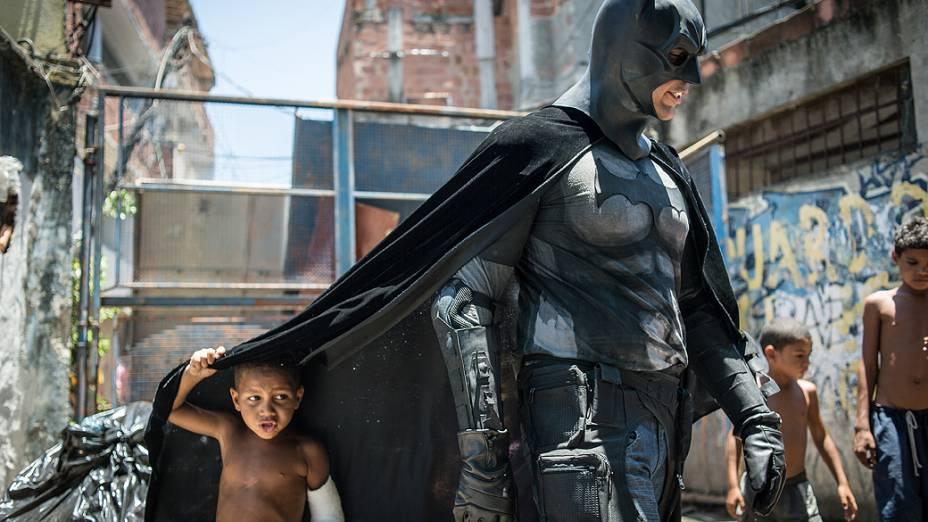 Crianças brincam em torno de um homem vestido de Batman na Favela do Metrô, área próxima ao estádio do Maracanã, no Rio de Janeiro. As famílias que vivem no local se recusam a ter suas casas demolidas, como parte do projeto de renovação do bairro antes da Copa do Mundo