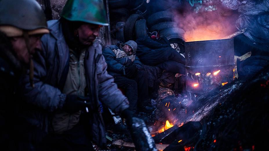 Manifestantes anti-governo se aquecem em um fogueira perto de uma barricada, em Kiev, na Ucrânia