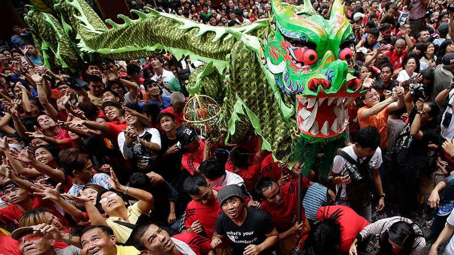 Pessoas tentam pegar envelopes com dinheiro e outros itens que são jogados enquanto seguem o dragão, durante a celebração do Ano Novo chinês, em um bairro chinês das Filipinas