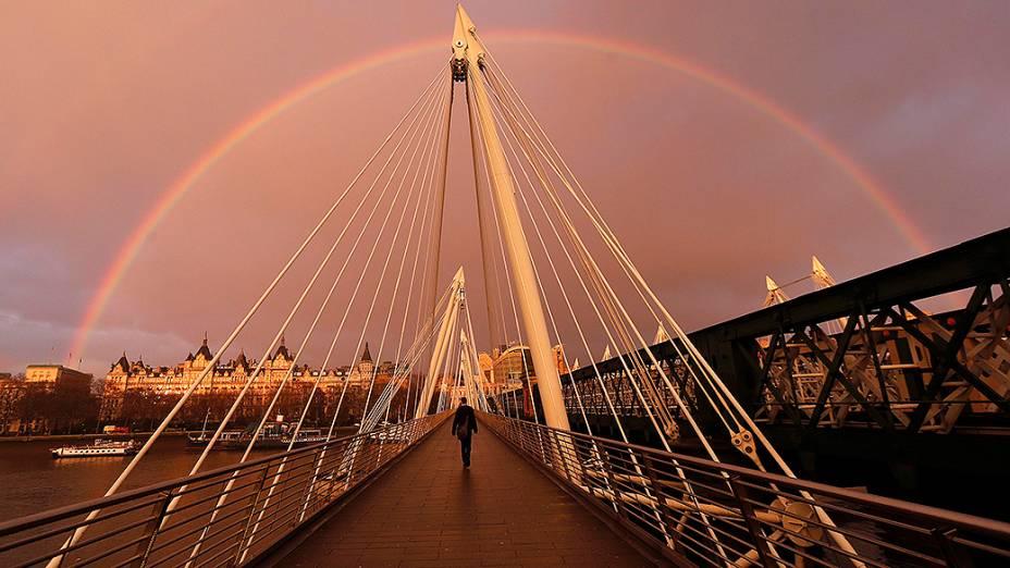Arco-íris aparece enquanto um pedestre atravessa a Ponte Hungerford em Londres