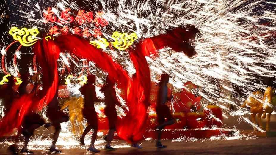 Dançarinos usam fogos de artifício durante uma performance para celebrar o tradicional Festival da Primavera, no primeiro dia do Ano Novo Lunar chinês, que saúda o Ano do Cavalo, no parque de diversões Happy Valley em Pequim