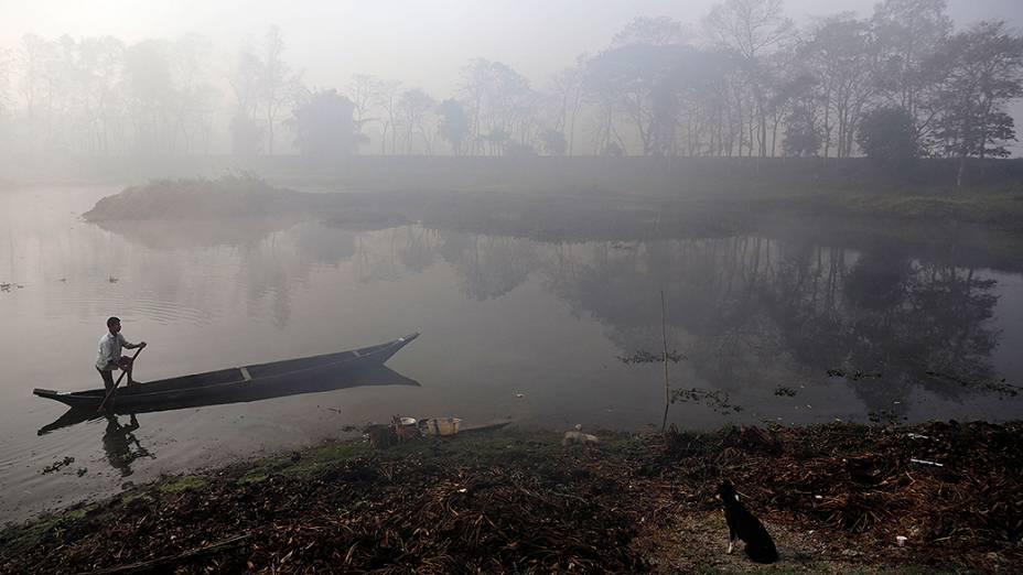 Homem atravessa o um rio sob nevoeiro nos arredores de Guwahati, na Índia