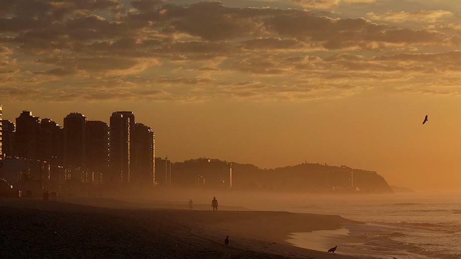 Homem caminha na praia da Barra da Tijuca praia durante o nascer do sol no Rio de Janeiro nesta sexta-feira (31)
