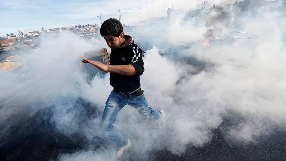 Manifestante palestino atravessa uma nuvem gás lacrimogêneo disparado por soldados israelenses durante confrontos em Jalazoun no campo de refugiados perto da cidade de Ramallah, na Cisjordânia