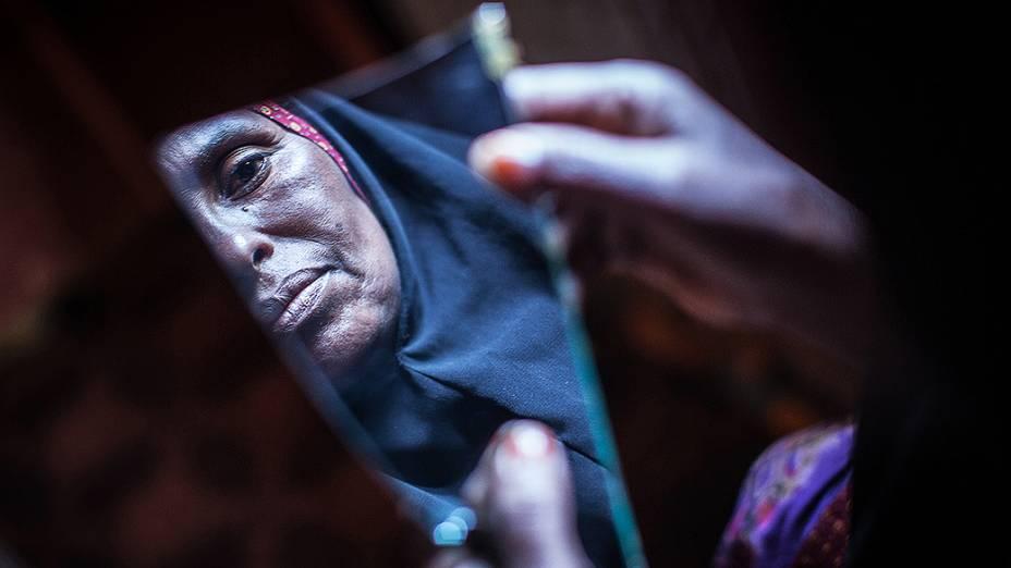 Amran Mahamood, que fez a vida por 15 anos por circuncidando meninas, olha para um pedaço de um espelho, em Hargeisa, na Somália
