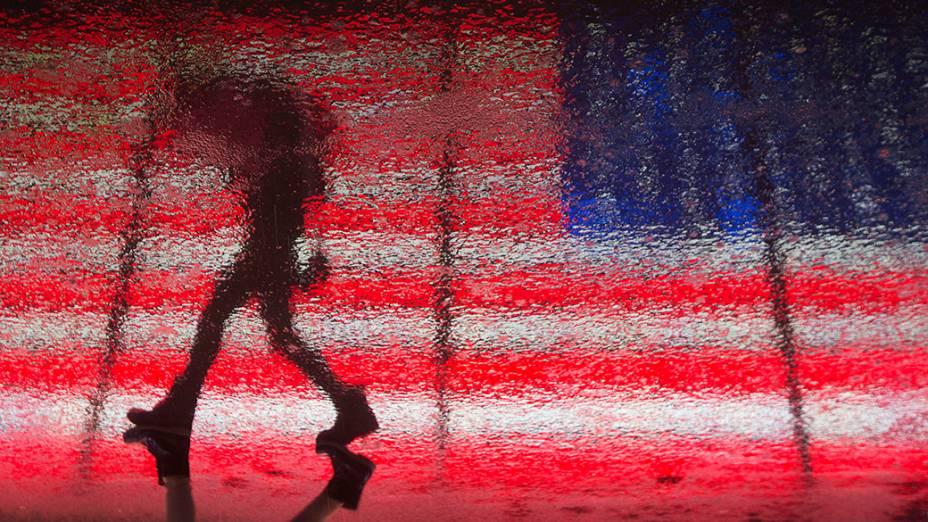 Mulher refletida no asfalto molhado enquanto passa por uma bandeira dos Estados Unidosa em Times Square durante uma tempestade de inverno em Nova York