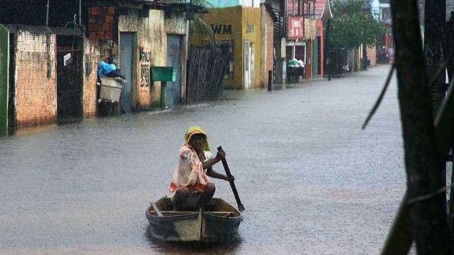 Moradora usa um barco para navegar entre ruas inundadas depois que o rio Acre transbordou devido às fortes chuvas, em Rio Branco, no Acre
