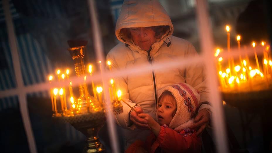 Mulher ajuda seu filho a acender uma vela dentro de uma igreja improvisada na Praça da Independência, o epicentro das manifestações em Kiev, na Ucrânia