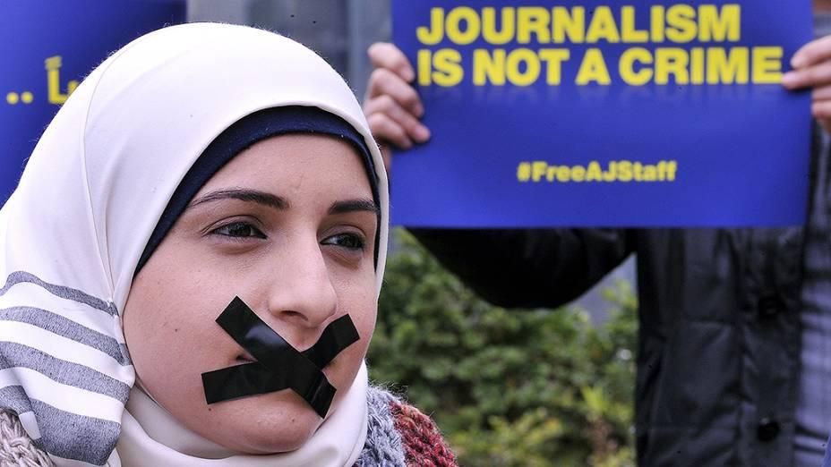 Ativista protesta contra a prisão de vinte jornalistas da Al Jazeera no Egito durante manifestação em favor da liberdade de imprensa em Beirute, no Líbano