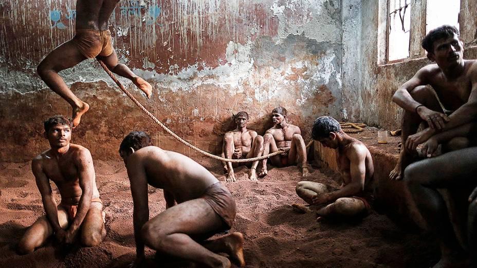 Lutadores de Kushti, atividade praticada na lama, em um centro de treinamento de Mumbai, na Índia