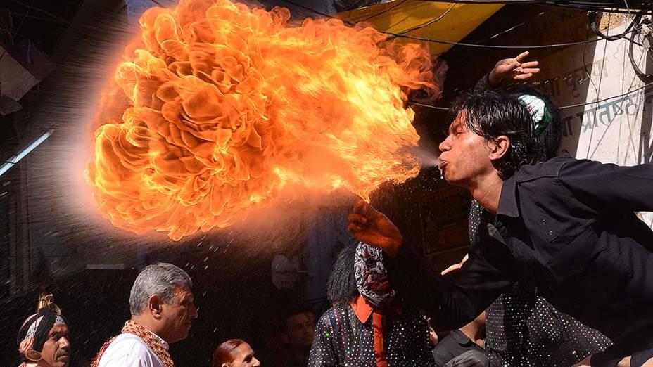 Devoto hindu cospiu fogo durante o festival Holi em Amritsar, na Índia