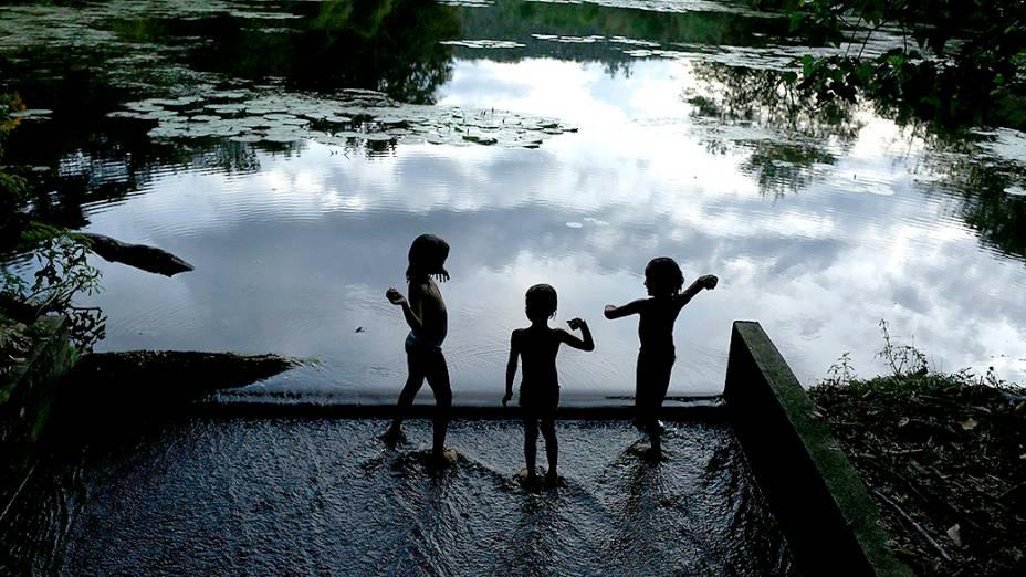 Crianças brincam na margem de uma lagoa na Reserva Ecológica de Guapiaçu, no Rio