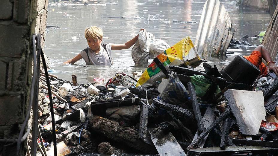 Menino procura objetos, após um incêndio destruir uma favela de Manila, nas Filipinas. Ao menos uma pessoa morreu e cerca de 1000 ficaram desabrigadas
