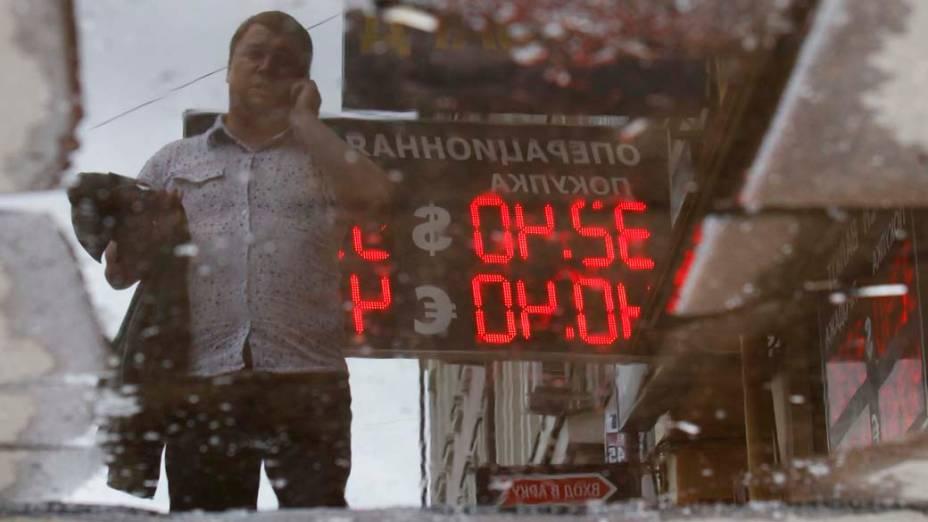 Painel com taxas de câmbio é visto em poça dágua em Moscou, na Rússia
