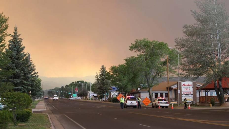 Policiais bloqueiam estrada a caminho de Eagar, Arizona. O incêndio que atingiu a região destruiu parte da floresta local e cerca de 2.000 moradores foram evacuados do local