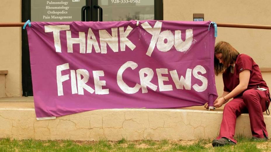 Funcionária de um hospital amarra cartaz em agradecimento aos bombeiros na cidade de Springerville, Arizona