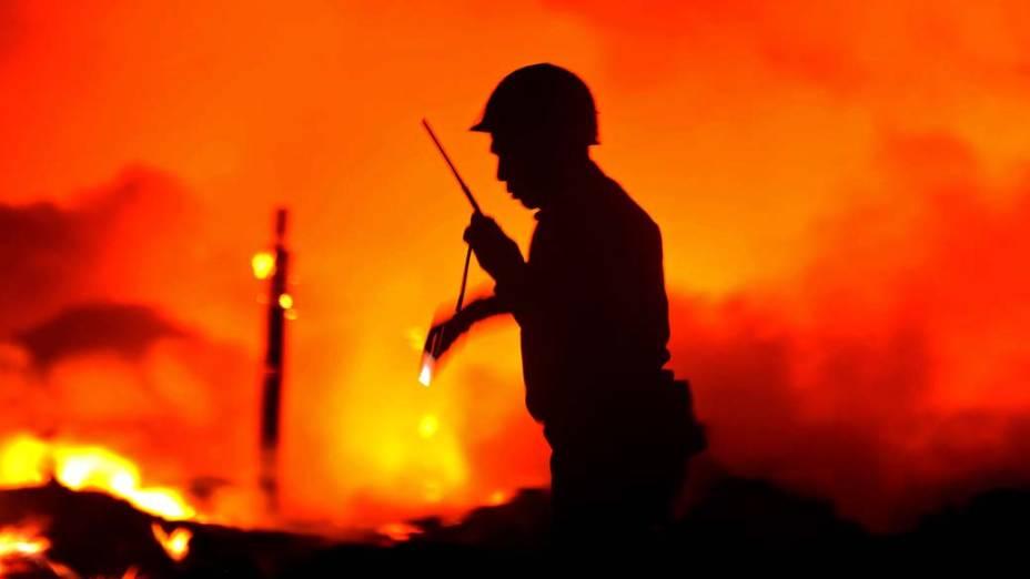 Bombeiros procuram por corpos depois de uma grande explosão seguida de incêndio em Yangun, Mianmar