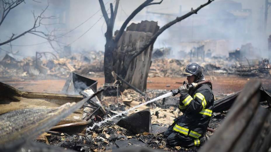 Bombeiro faz trabalho de rescaldo na favela do Moinho, São Paulo