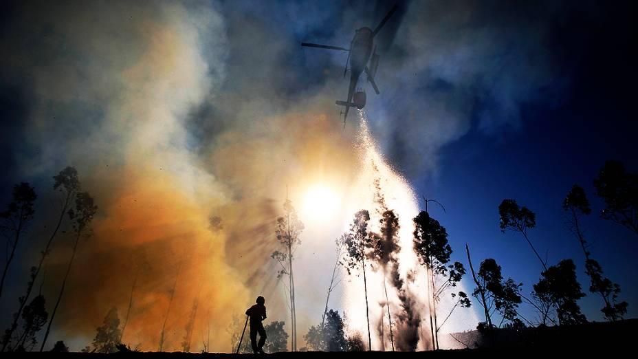 Helicóptero despeja água sobre vegetação em chamas em Alvaiazere, perto de Ourem, em Portugal. Uma pessoa morreu e três ficaram feridas. O governo português solicitou a outros países europeus que enviem ajuda para extinguir o incêndio