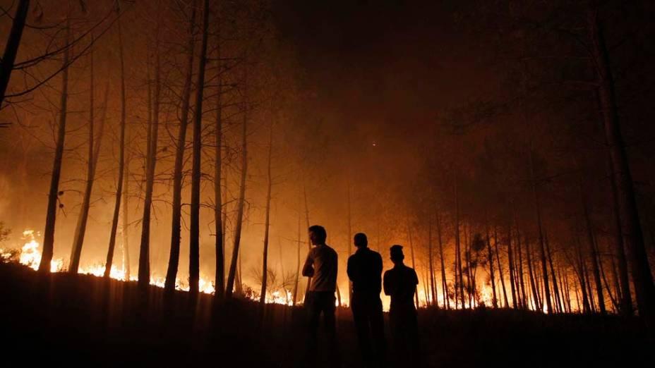 Moradores observam incêndio que já destruiu mais de 3.000 hectares em Povoa de Calde, em Portugal