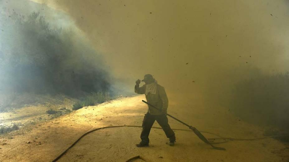 Bombeiro caminha em área incendiada no parque natural da Serra do Gerês em Lindoso, Portugal. Cerca de 650 profissionais trabalham para conter o fogo que se espalha no país desde a semana passada
