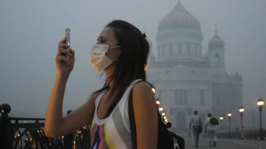 Garota usa máscara para se proteger contra a fumaça em Moscou