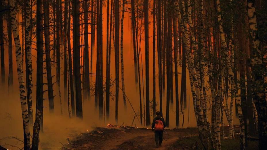 Homem caminha em floresta em chamas próxima ao vilarejo de Golovanovo, na Rússia