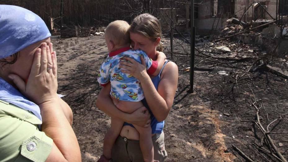Mulheres choram ao encontrar suas casas queimadas em Voronezh, na Rússia