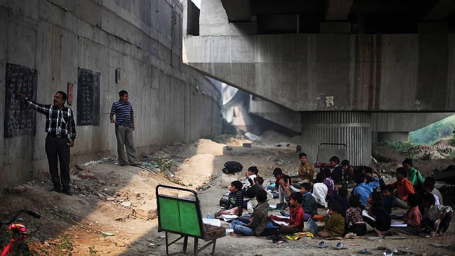 Alunos participam de aula gratuita para crianças pobres, debaixo de um viaduto em Nova Déli, Índia