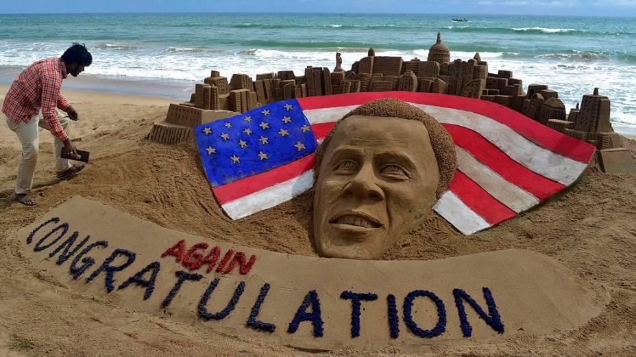 Artista indiano faz os retoques finais em escultura de areia feita em homenagem ao presidente reeleito dos Estados Unidos, Barack Obama, na praia de Puri, na Índia