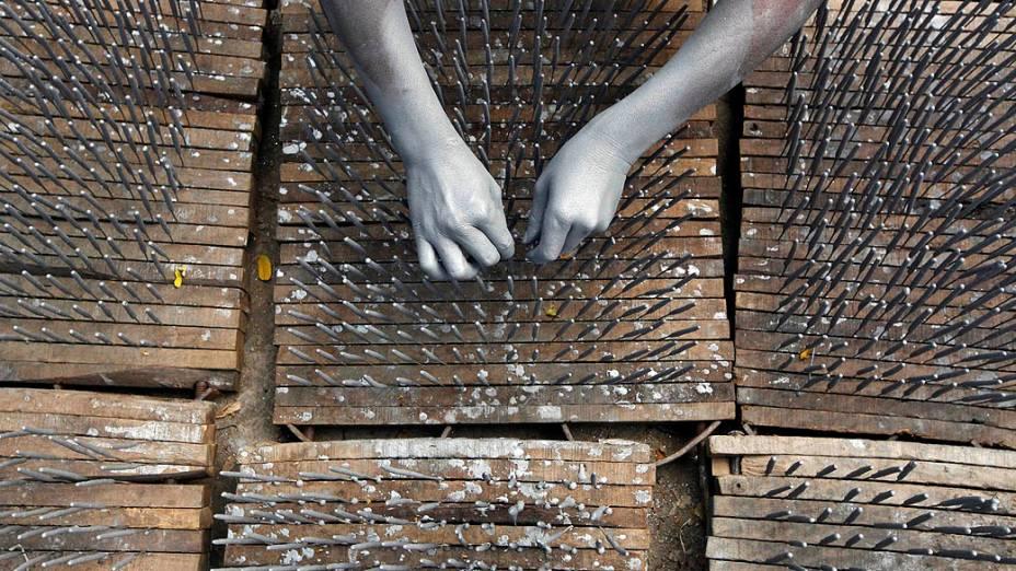 Trabalhador de uma fábrica de fogos-de-artifício em Calcutá, Índia