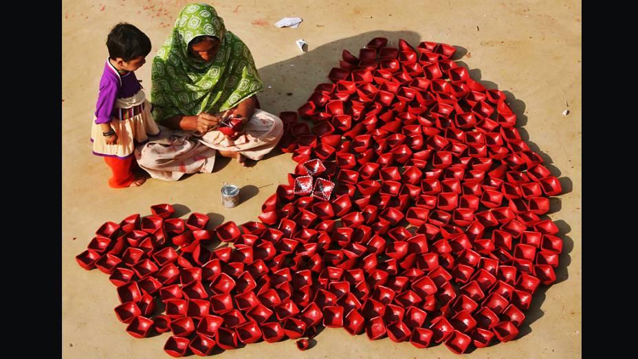 Mulher pinta lâmpadas de argila com sua filha, na periferia de Jammu, Índia