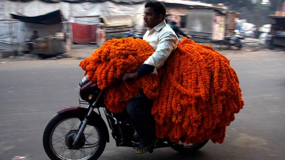 Vendedor transporta arranjos com flores de  calêndulas na cidade indiana de Allahabad