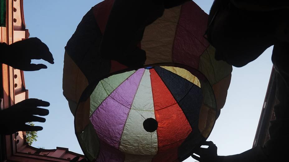 Membros de uma família lançam lanterna para o céu durante Diwali em Calcutá