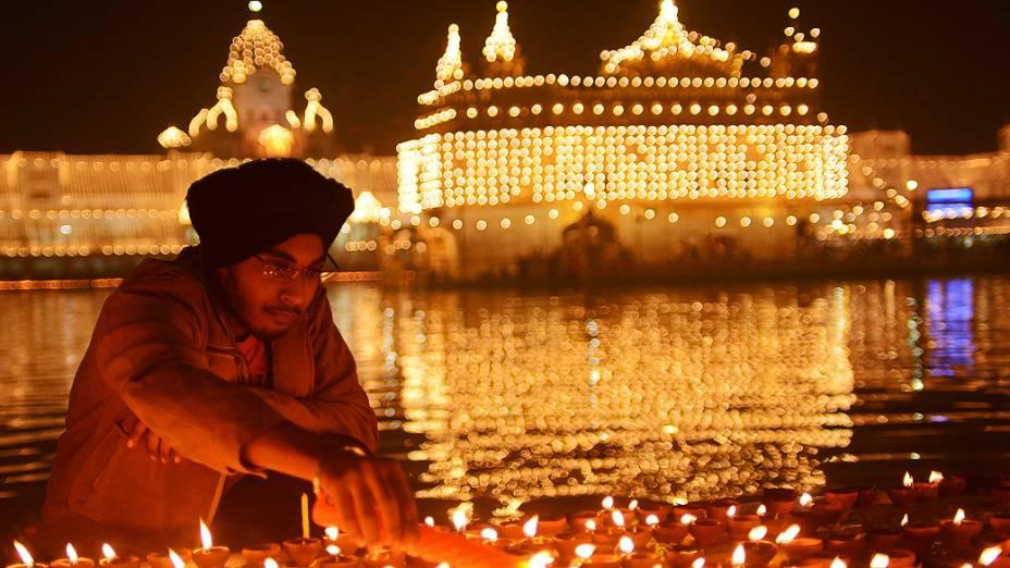 Devoto indiano sikh acende lâmpadas no Templo Dourado de Amritsar