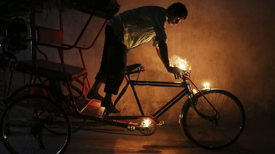 Indiano coloca velas em sua bicicleta para obter boa sorte e fortuna durante o festival Diwali, em Nova Délhi