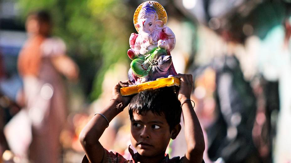 Menino carrega estátua do deus Ganesh, durante celebração de Ganesh Chaturthi Festival em Jammu, na Índia
