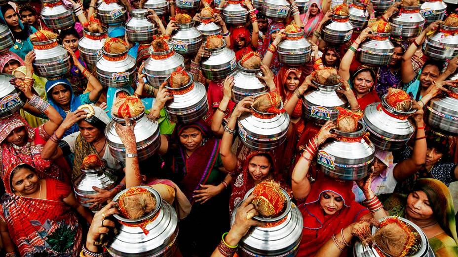 Mulheres indianas carregam potes de água e cocos em um ritual hindu em Nova Délhi, na Índia