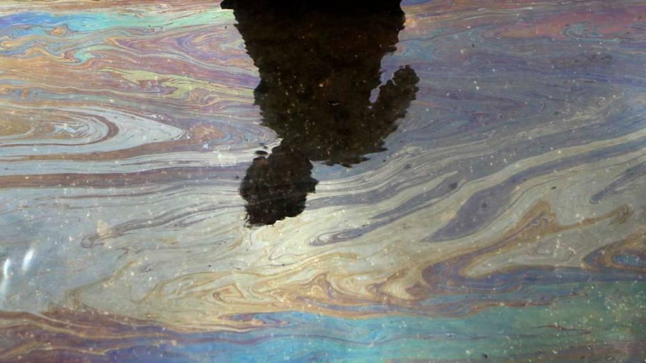 Garoto observa sua sombra refletida em mancha de óleo na costa de Mumbai, na Índia. A região foi contaminada pelo vazamento do navio MSC Chitra, que se chocou com outra embarcação. Segundo o governo local, as perdas já foram controladas mas a pesca ainda não está liberada na região