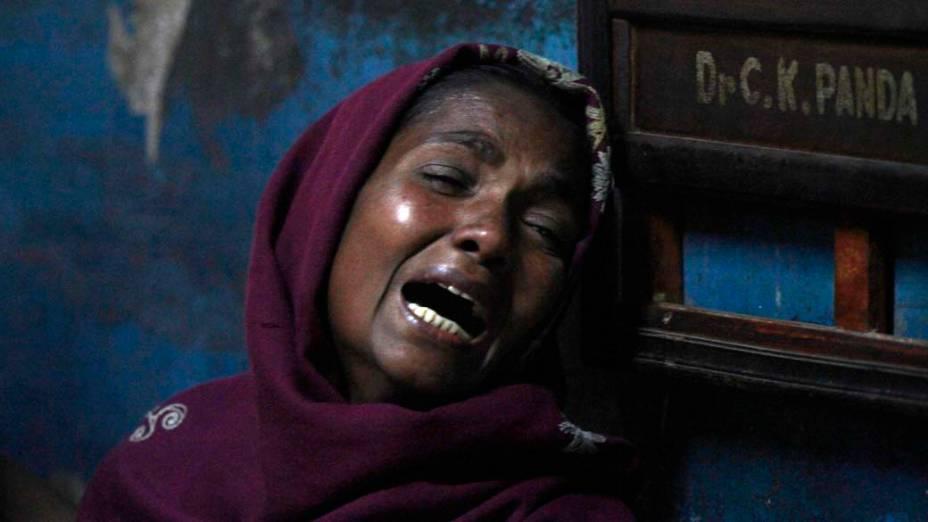 Mulher chora por parente que morreu, ao consumir bebida alcoólica adulterada, em hospital de Porto Diamante, Índia