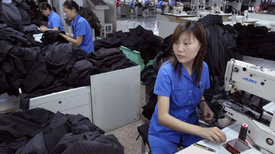 """<strong>PROTECIONISMO</strong> – """"O nosso sistema de proteção social, as normas ambientais e de segurança fazem com que o nosso produto tenha mais custos do que aqueles produzidos nos países emergentes"""", diz Marine Le Pen. Na foto, funcionária da indústria têxtil na cidade chinesa de Jiangyin"""