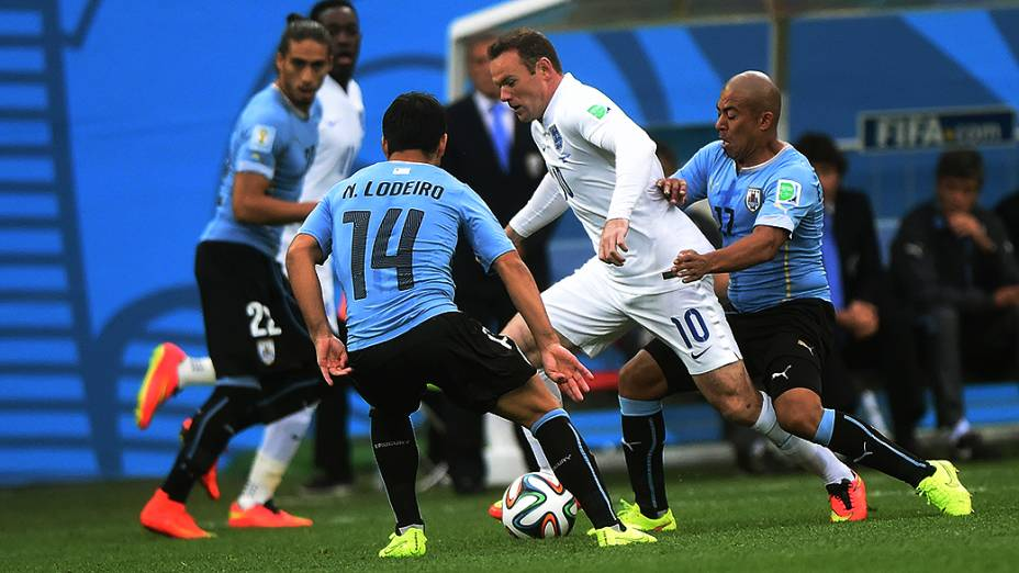 O inglês Wayne Rooney é marcado por dois jogadores do Uruguai no Itaquerão, em São Paulo