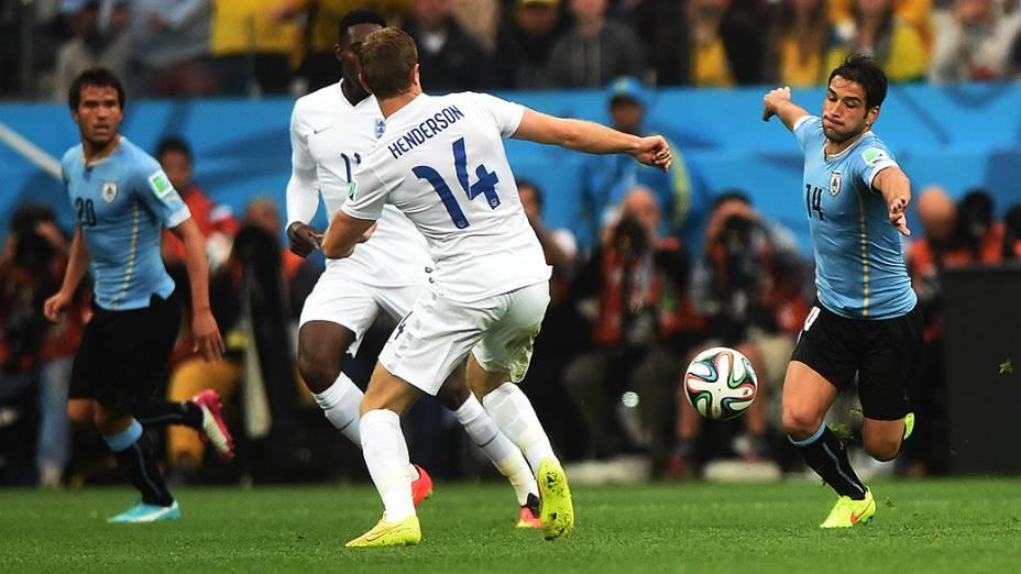 O inglês Henderson disputa a bola com Lodeiro, do Uruguai, no Itaquerão em São Paulo