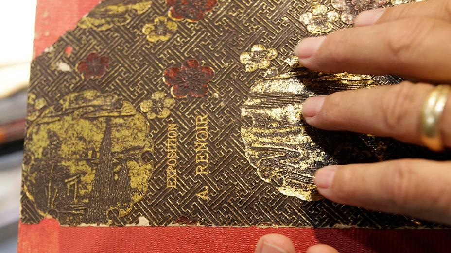 Brian Roughton, diretor de belas artes da casa de leilões Heritage Auctions, segura um caderno que pertenceu a Pierre-Auguste Renoir. O arquivo pessoal do artista francês vai a leilão nos Estados Unidos