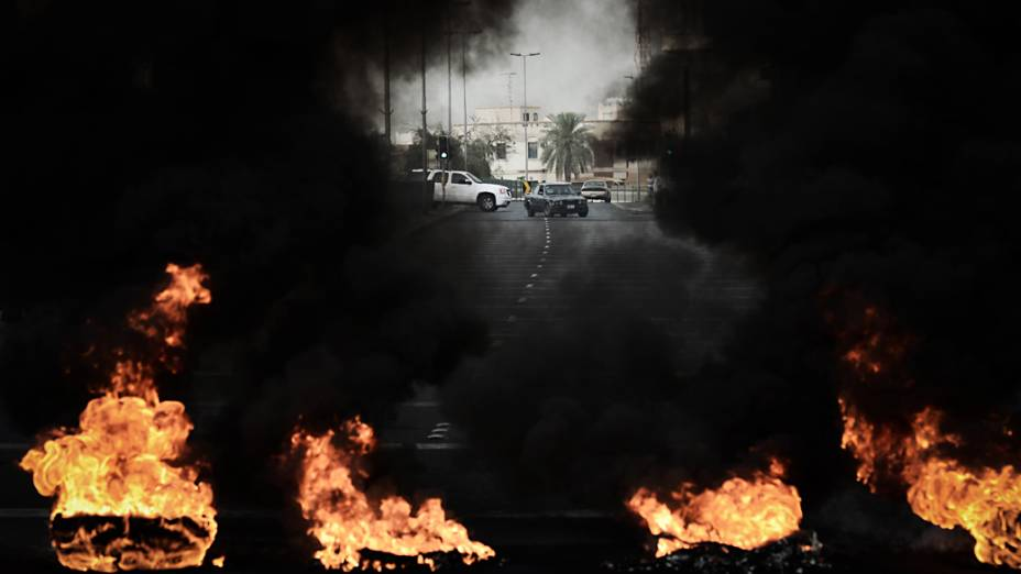 Pneus são queimados em uma estrada durante confrontos entre manifestantes e policiais do Bahrein após um protesto contra a realização do GP de Fórmula 1 no país