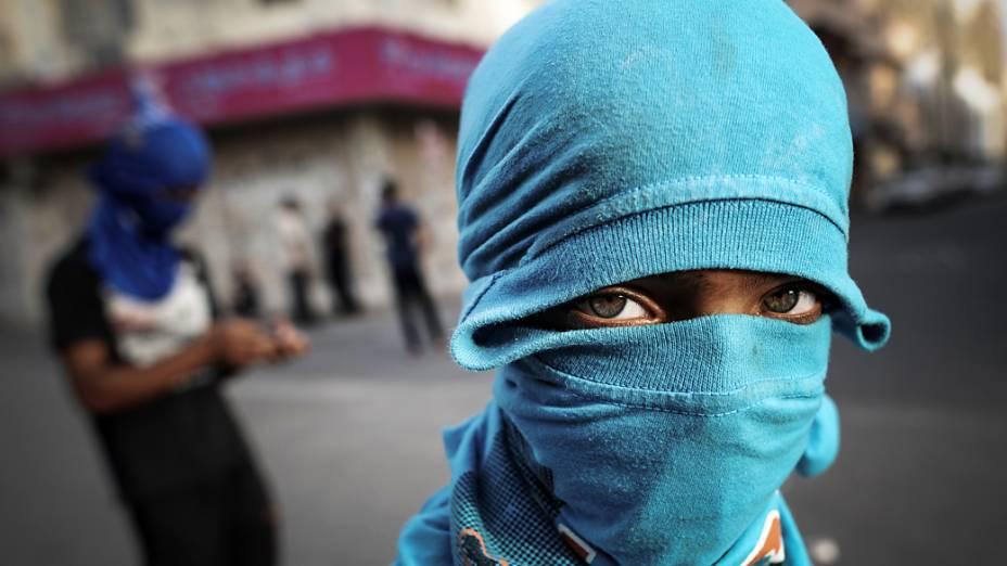Homem cobre o rosto durante confrontos entre manifestantes e policiais do Bahrein após um protesto contra a realização do GP de Fórmula 1 no país