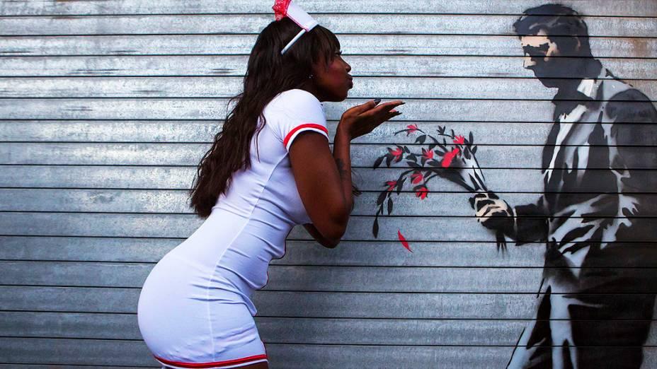 Dançarina posa em uma instalação do artista britânico Banksy na porta da frente do Clube Hustler em Nova York