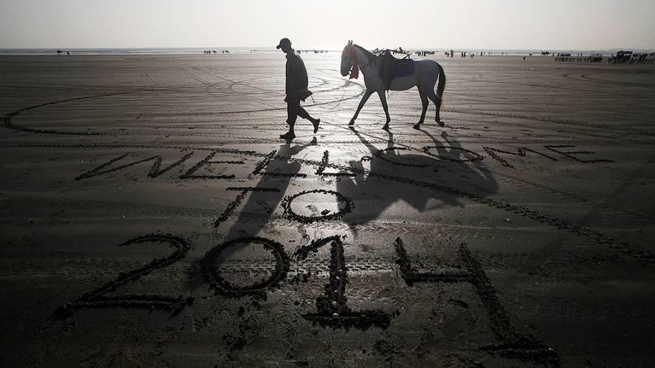Homem conduz seu cavalo por uma praia com uma mensagem deixada por um visitante na areia na véspera do Ano Novo, em Karachi, Paquistão