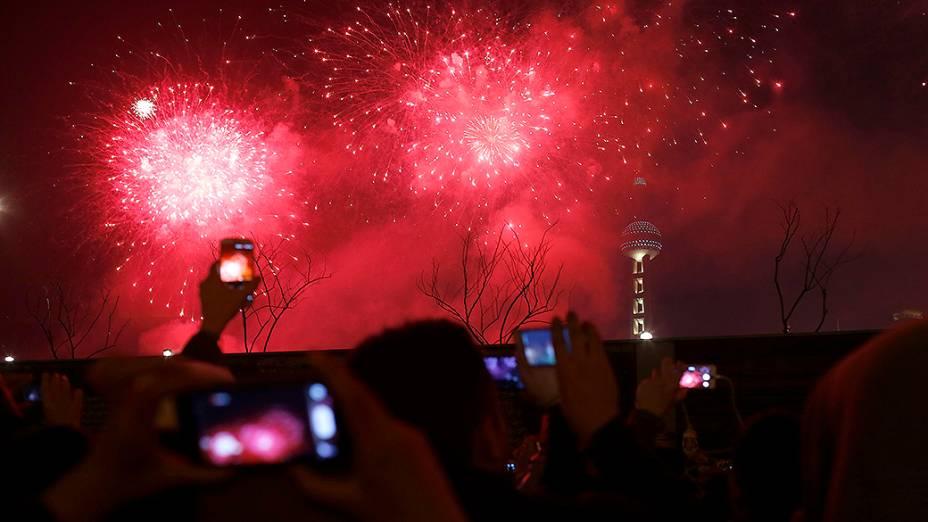 Visitantes tiram fotos e vídeos, do show de fogos de artifício sobre Oriental Pearl Tower, em Xangai, na China
