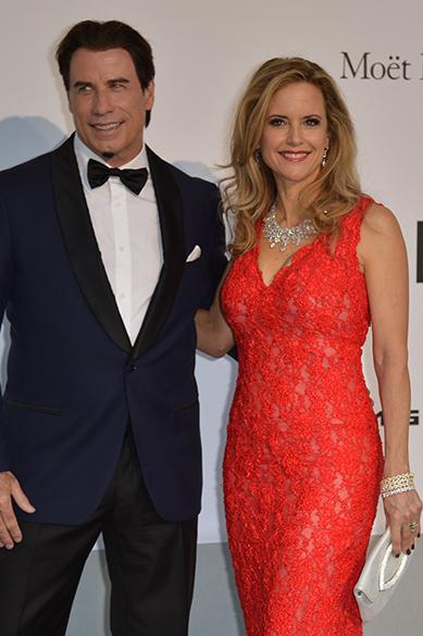 O ator americano John Travolta e a mulher Kelly Preston chegam para a amfAr 21 durante o 67º Festival de Cinema de Cannes, na França